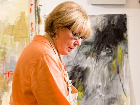 Photograph of abstract painter Karen Stastny at work in her studio.